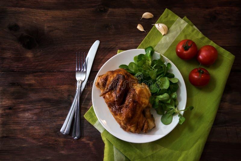 Medio pollo asado a la parrilla con los tomates, la ensalada de maíz y el ajo, blancos imagenes de archivo
