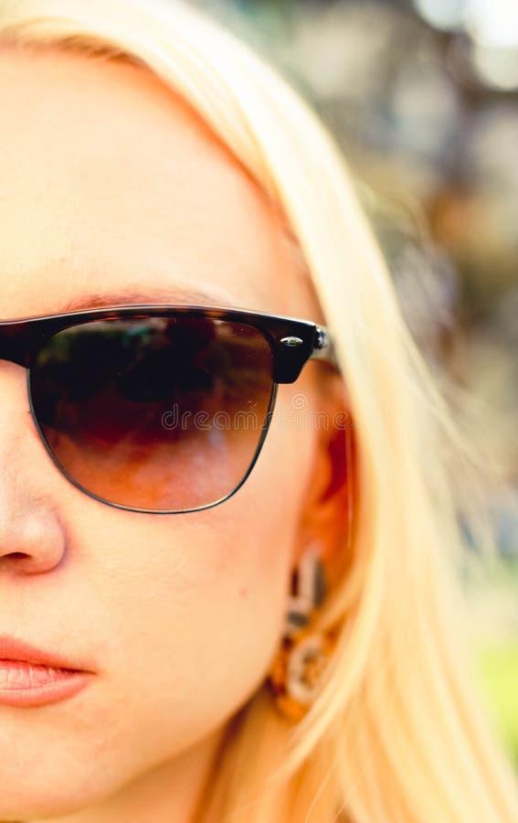Medio portrate de la cara de la mujer rubia de la moda en vidrios de sol foto de archivo libre de regalías