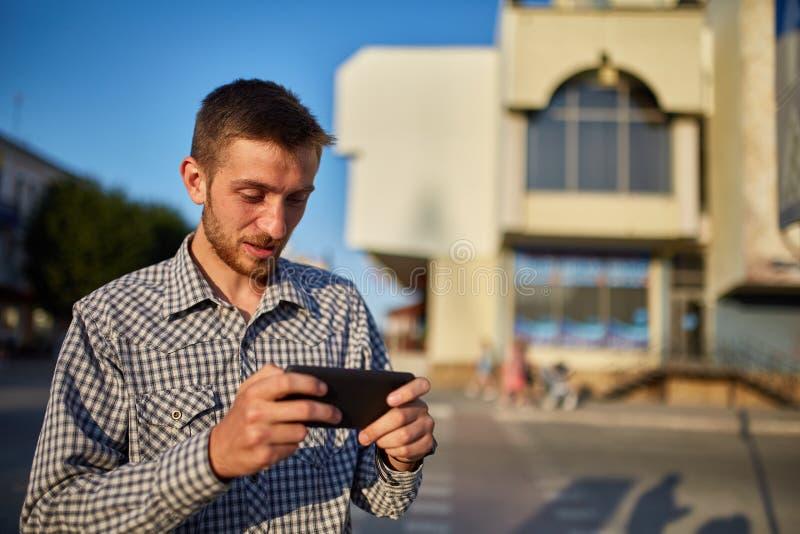 Medio retrato de la longitud del varón barbudo en ropa casual usando el teléfono de célula mientras que se coloca en el ambiente  fotos de archivo libres de regalías