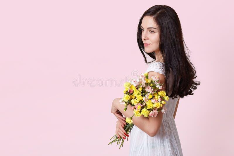 Medio retrato de la longitud de la mujer morena encantadora en los sundress blancos que sostienen el ramo de flores sobre fondo r fotos de archivo libres de regalías