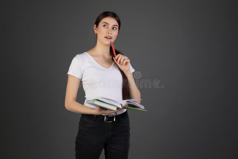 Medio retrato de la longitud de la mujer soñadora thougtful que sostiene la pluma roja a disposición cerca de la boca, libros en  fotos de archivo
