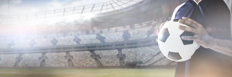 Medio sectie van de bal van de voetbalsterholding tegen mening van een stadion royalty-vrije stock foto