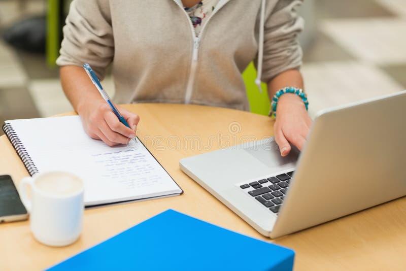 Medio sectie van een vrouwelijke student die thuiswerk doen door laptop royalty-vrije stock foto