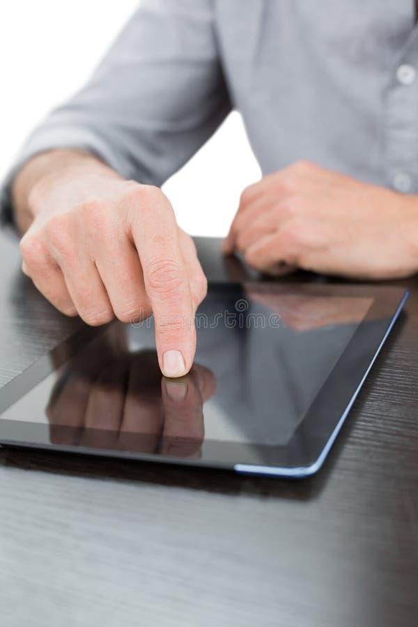 Medio sectie van een zakenman die digitale tablet gebruiken bij lijst royalty-vrije stock foto
