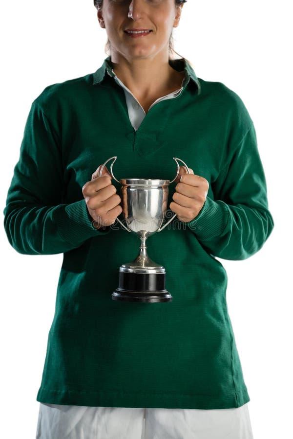 Medio sectie van het glimlachen van vrouwelijke de holdingstrofee van de rugbyspeler stock afbeelding