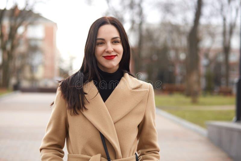 Medio tiro de la longitud de la mujer joven atractiva en capa beige elegante que camina en la calle La mujer morena adorable pasa imagen de archivo libre de regalías
