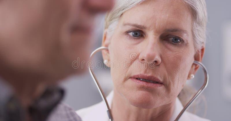 Medio-verouderde arts die aan mannelijke patiënt spreken stock afbeeldingen