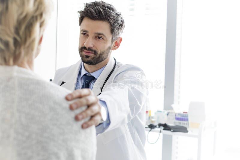 Medio volwassen arts die rijpe patiënt troosten bij het ziekenhuis royalty-vrije stock foto