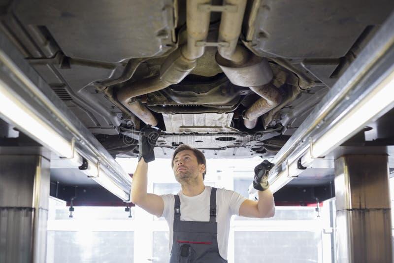 Medio volwassen mannelijke reparatiearbeider die auto in workshop herstellen stock afbeeldingen