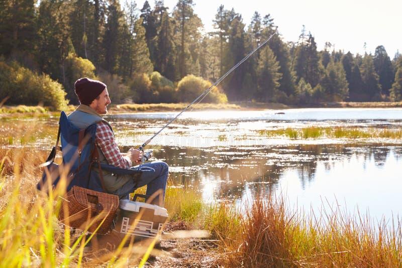 Medio-volwassen mens die door oever van het meer, Grote Beer, Californië, de V.S. vissen royalty-vrije stock afbeelding