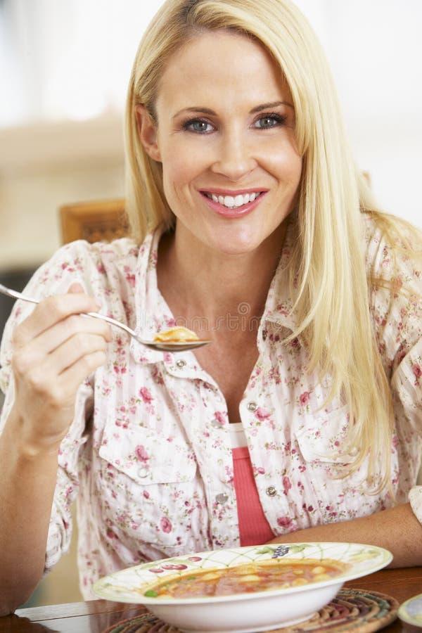 Medio Volwassen Vrouw die Soep eet, die bij de Camera glimlacht stock foto's