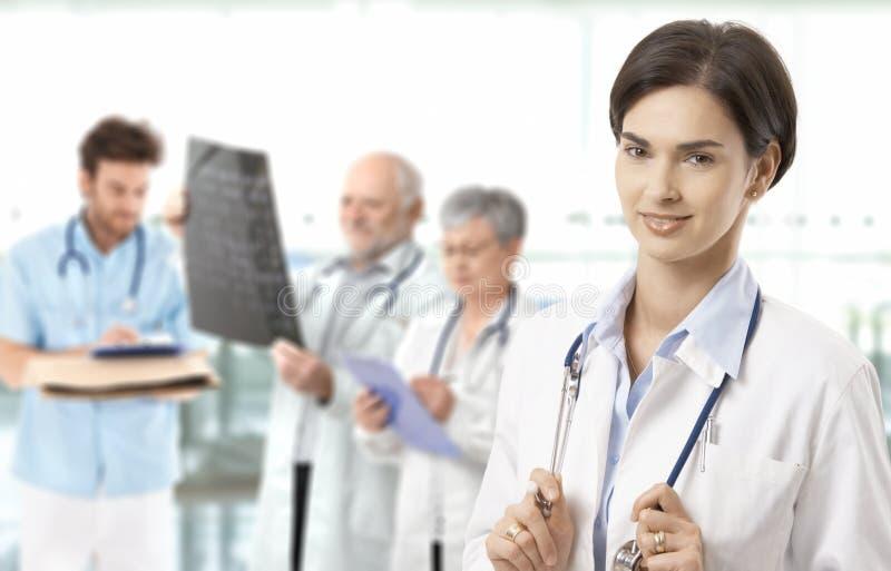 Medio-volwassen vrouwelijk artsen medisch team op achtergrond stock foto's