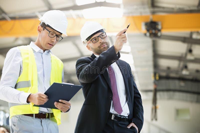 Medio volwassen zakenman met supervisor die bespreking in de metaalindustrie hebben royalty-vrije stock afbeelding