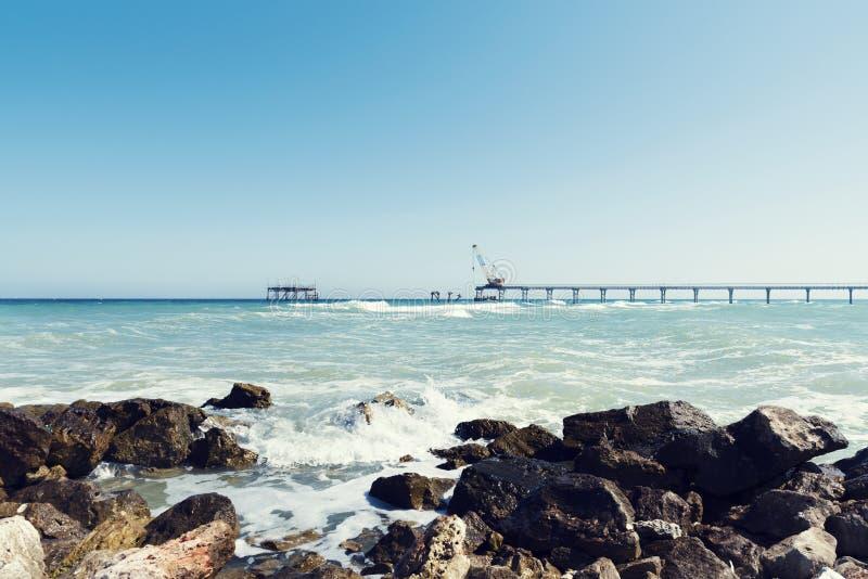 Mediodía del paisaje del mar con las ondas de las rocas y las construcciones del nuevos embarcadero y gaviotas imágenes de archivo libres de regalías