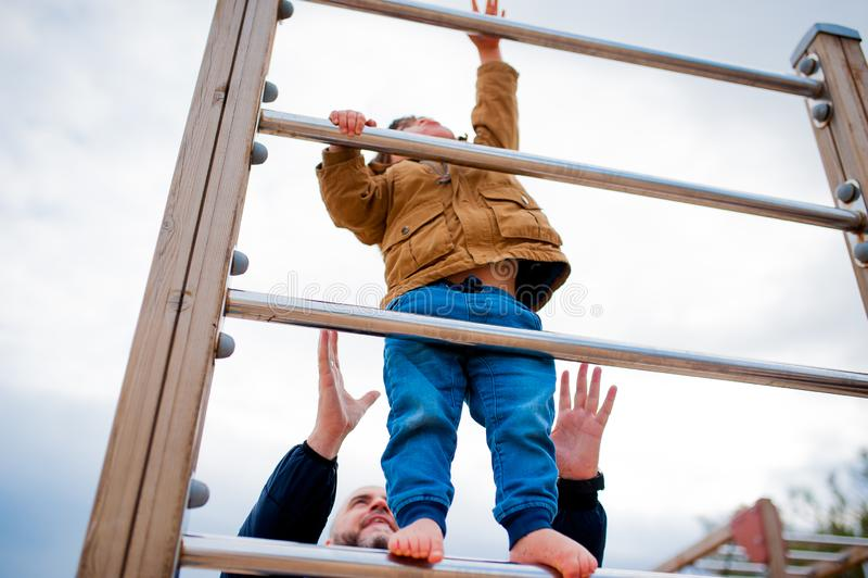 Mediolan, Włochy - 20 2018 Listopad: potomstwa ojcują pomoc syna wzrastać w górę i dosięgać wierzchołek gra w outdoors parku podc zdjęcia stock