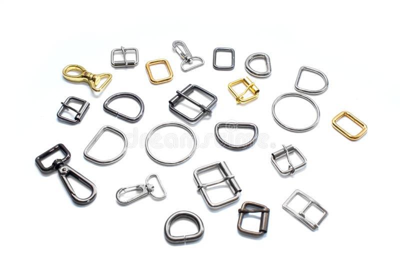 Medios anillos, hebillas y carabinas del metal en un fondo blanco Vista lateral fotos de archivo libres de regalías