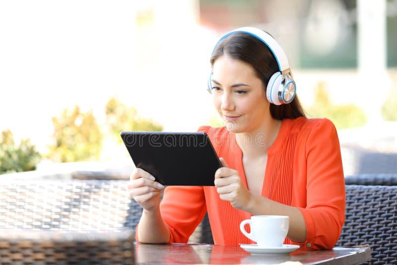 Medios de observación y que escuchan de la mujer en una tableta en una barra imagenes de archivo