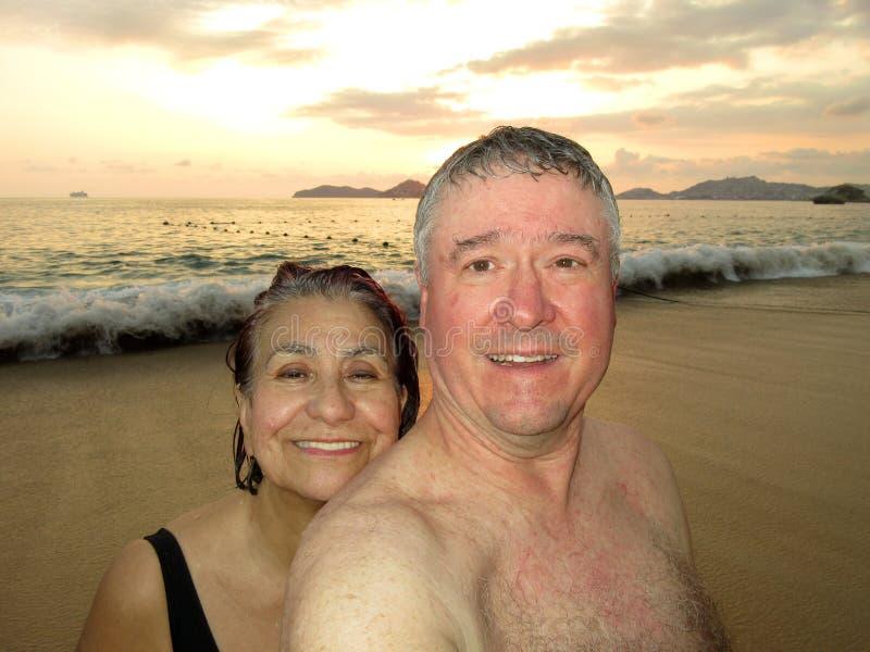 Medios envejecidos se juntan en la puesta del sol en Acapulco fotografía de archivo