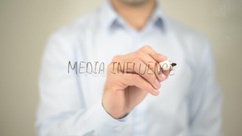 Medios Influnce, escritura del hombre en la pantalla transparente foto de archivo