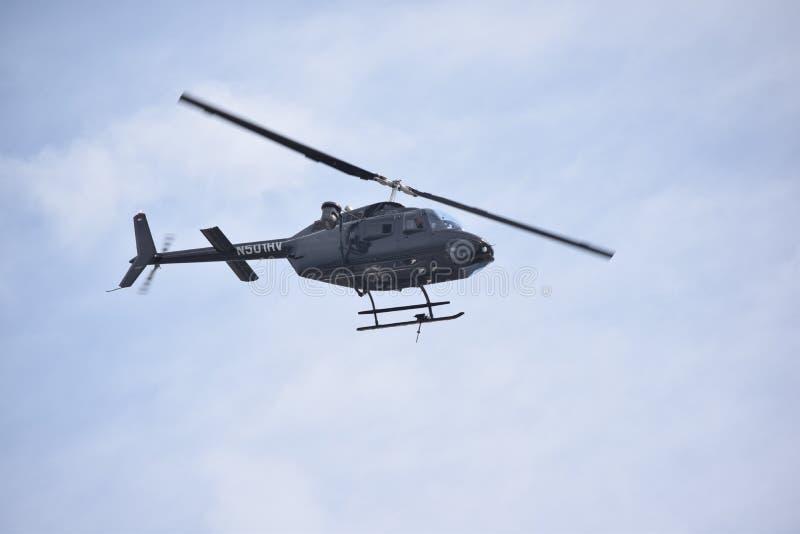 Medios vuelo del helicóptero a través de los cielos azules imagenes de archivo