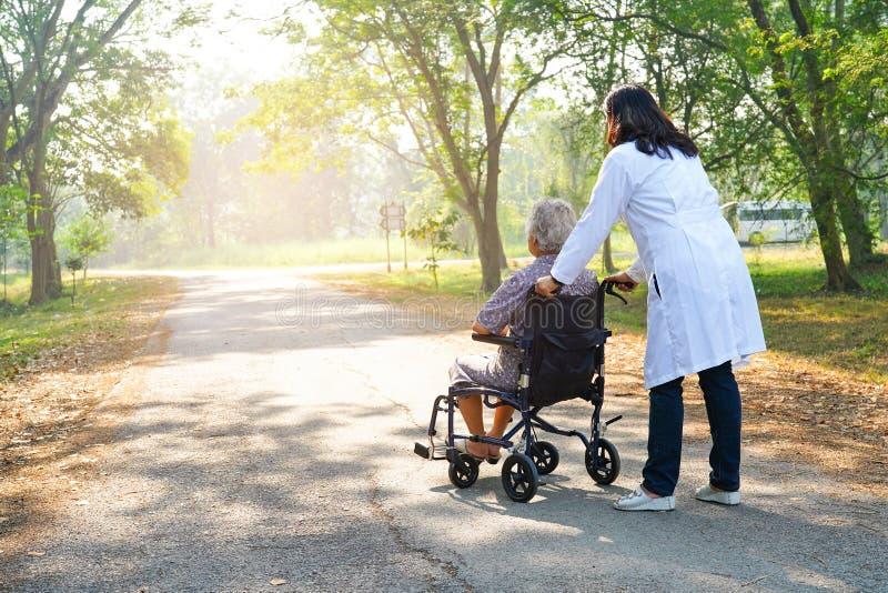 Medique a ajuda e importe-se o paciente superior ou idoso asi?tico da mulher da senhora idosa que senta-se na cadeira de rodas na fotos de stock