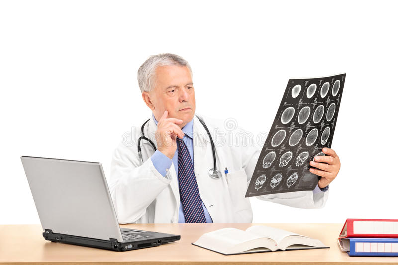 Medique a análise de um raio X assentado em uma tabela imagem de stock