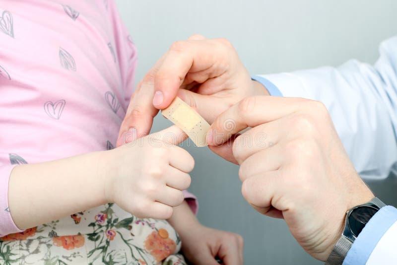 Medique a colocação ao emplastro da menina sobre o dedo dorido fotografia de stock royalty free