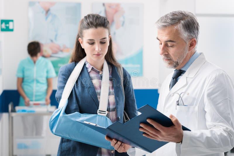 Medique com um paciente com braço quebrado fotografia de stock royalty free