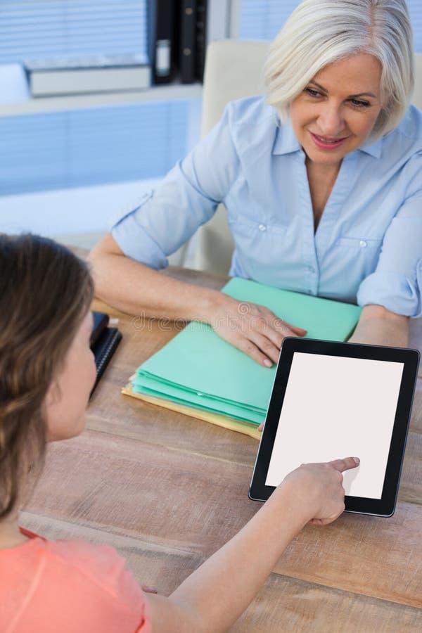 Medique a discussão com o paciente sobre a tabuleta digital no hospital fotos de stock