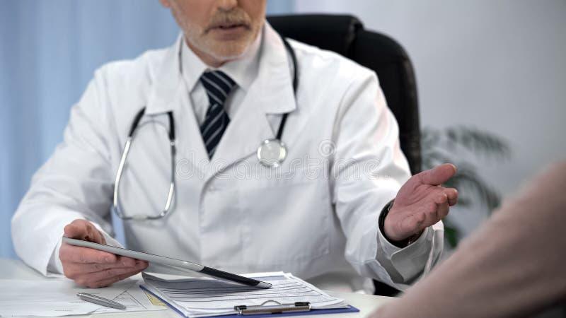 Medique dizer o diagnóstico ao paciente, discutindo benefícios do tratamento cirúrgico imagem de stock