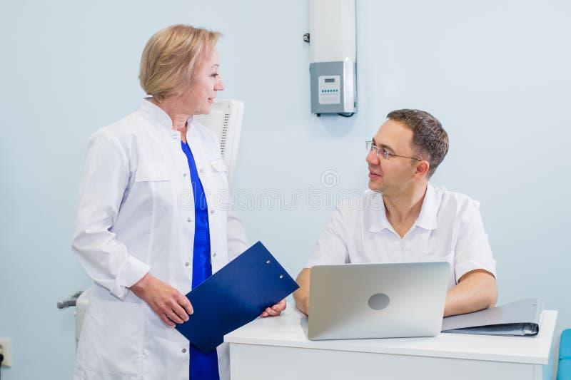Medique e nutra a revisão da informação paciente em um laptop em um ajuste do escritório fotografia de stock royalty free