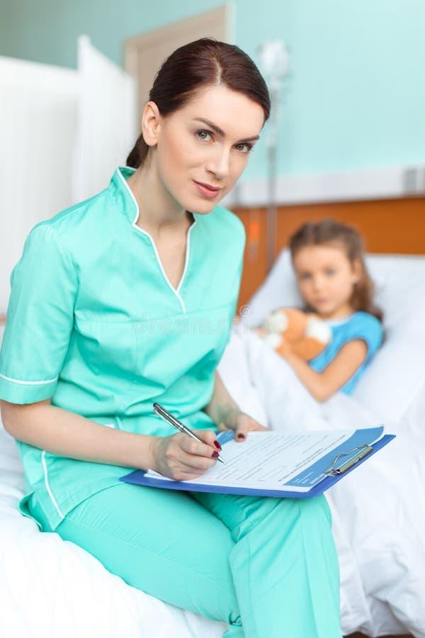 Medique a escrita no diagnóstico da prancheta da menina doente imagem de stock
