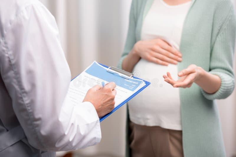 Medique a escrita para baixo de queixas da mulher gravida durante a consulta médica imagem de stock