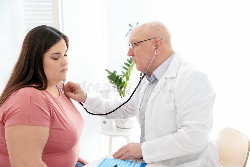 Medique a escuta a pulsação do coração paciente do ` s com estetoscópio fotografia de stock royalty free