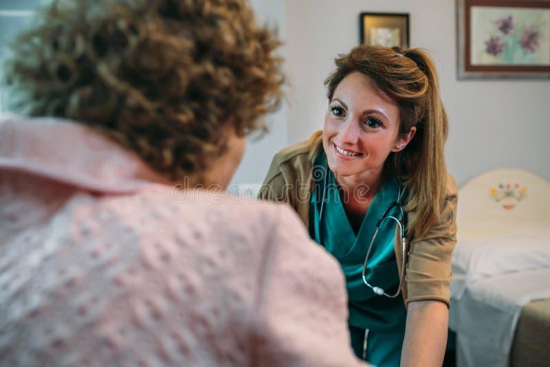 Medique a fala ao paciente idoso em uma cadeira de rodas fotografia de stock