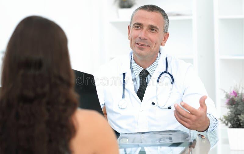 Medique a fala ao paciente que senta-se na tabela imagem de stock royalty free