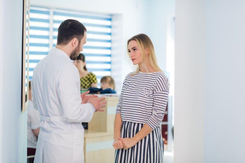 Medique a fala a um paciente em um corredor foto de stock