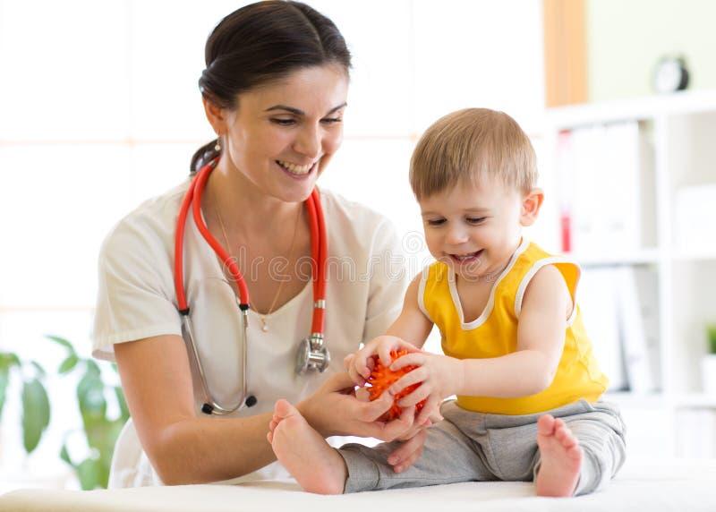 Medique fazer a massagem ao paciente pequeno que usa uma bola imagem de stock royalty free