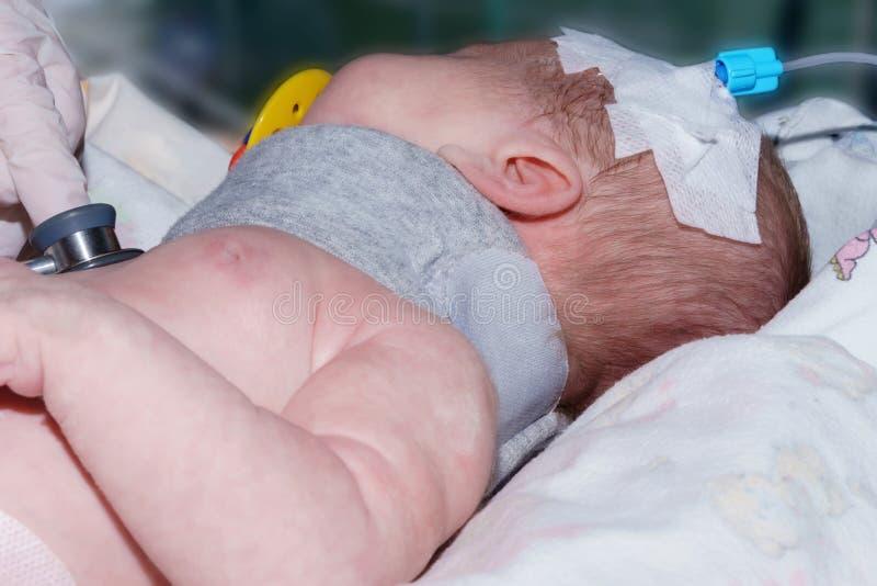 Medique fazer o bebê recém-nascido da auscultação com o cateter intravenoso periférico e o colar ortopédico na unidade de cuidado fotos de stock