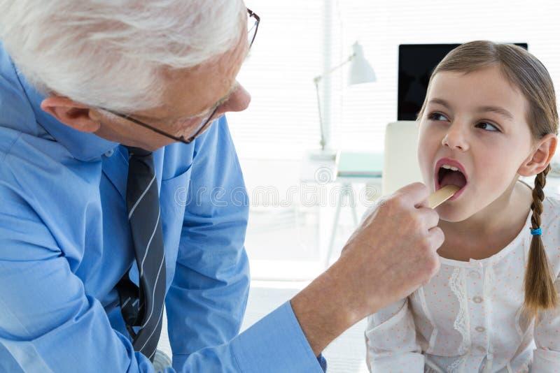 Medique a garganta paciente de exame usando o depressor de língua imagens de stock royalty free