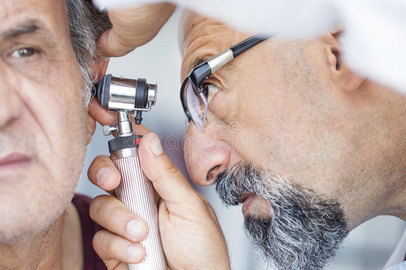 Medique guardar o otoscope e examinar a orelha do homem superior foto de stock