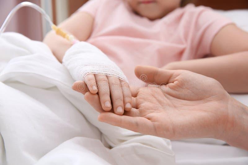Medique guardar pouca mão de criança com gotejamento intravenoso no hospital foto de stock