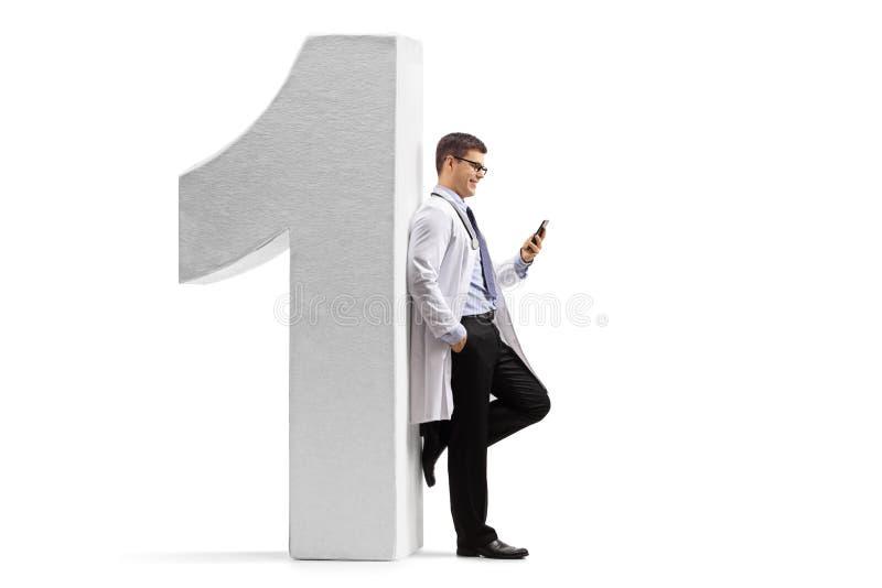 Medique a inclinação contra uma figura do número um e a utilização de um telefone imagens de stock