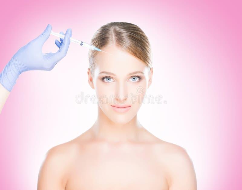 Medique a injeção em uma cara bonita de uma jovem mulher Plástico s foto de stock royalty free