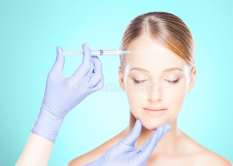 Medique a injeção em uma cara bonita de uma jovem mulher Plástico s foto de stock