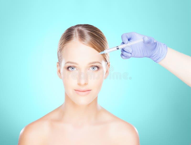 Medique a injeção em uma cara bonita de uma jovem mulher Plástico s imagens de stock