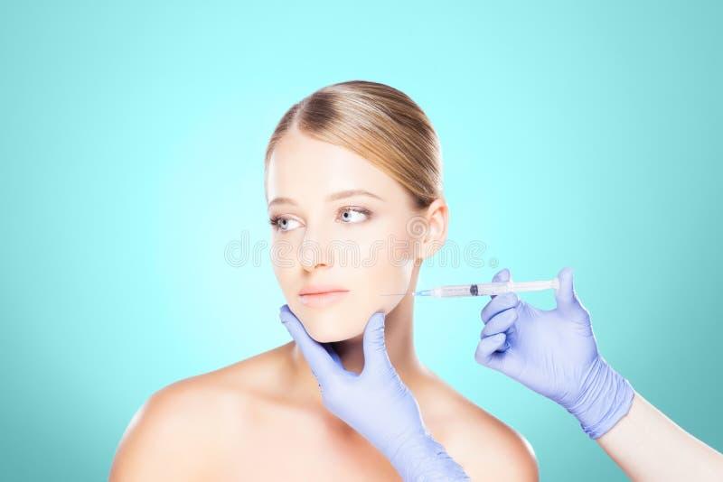 Medique a injeção em uma cara bonita de uma jovem mulher Plástico s fotografia de stock