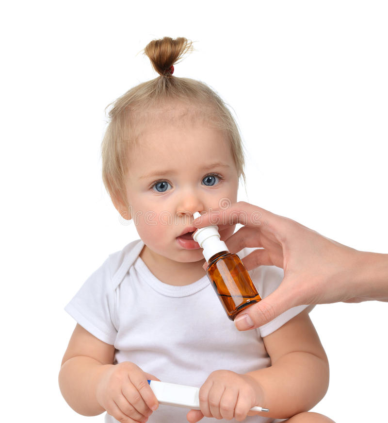 Medique a mão de Woman usando o pulverizador de nariz da medicina nasal para o toddl do bebê foto de stock royalty free