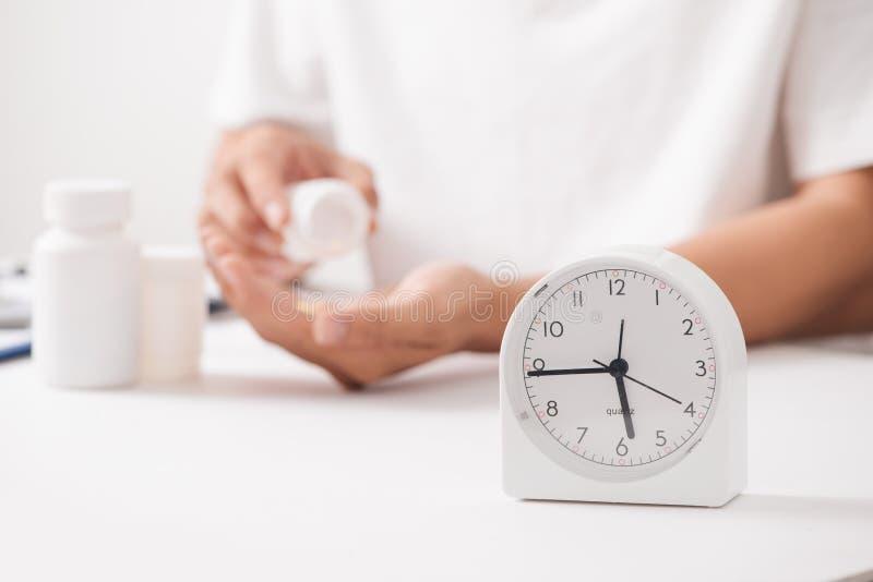 Medique a mão que guarda o comprimido do fitoterapia com pulso de disparo e garrafa, imagem de stock