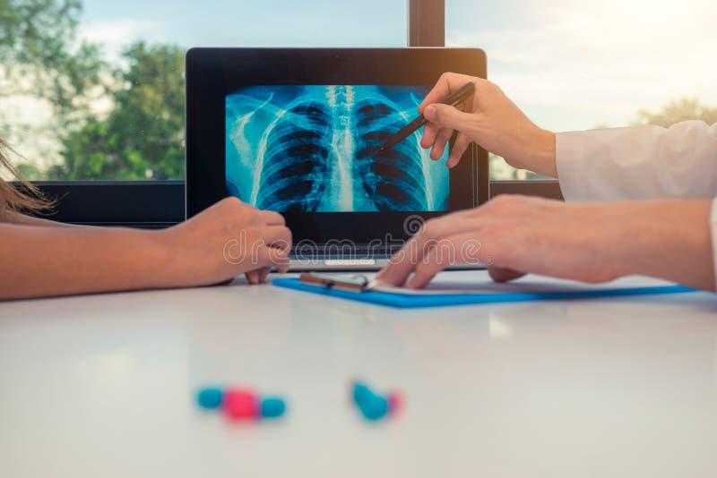 Medique mostrar um raio X dos pulmões e da caixa em um portátil a um paciente da mulher Comprimidos na mesa imagem de stock